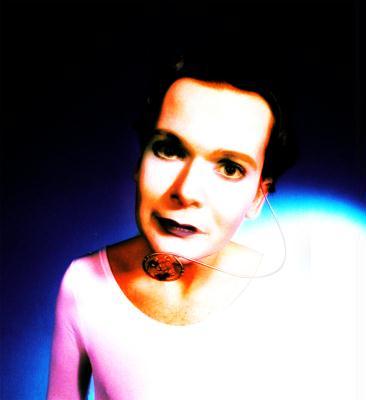 © Toni Seppi 1997 — © Dieter Telfser 2004 — Maske: Martin Geisler.  Die Rose als Mikrofon wäre immer schon mein Traum für wahre verbindliche Sprachtechniken gewesen. Der hier umgebaute Ohrsprecher diente als Kontrastwert zu den üblich eingesetzten. Es war bereits 1997 möglich Dinge zu benutzen, die es gar noch nicht in dieser Form gab. Ich warte nach wie vor auf das Implantat als Zahninlay, das die terrestrische Kommunikation für sich abdeckt. Es ist für mich keine Leistung sich mit Magnetstrahlung umgeben zu müssen, nur weil man mitteilen will, dass man sowieso zu spät dran ist. Ich bin sehr glücklich mit meinem Telefon im Vorzimmer.
